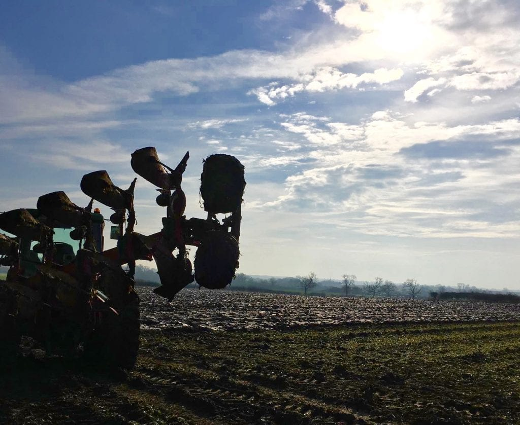 Ploughing in a field on a sunny day